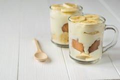 2 стеклянных чашки с пудингом банана и деревянной ложкой на белой таблице Десерт молока и банана Стоковые Изображения