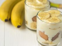 2 стеклянных чашки с пудингом банана и 2 зрелыми бананами на белой таблице Стоковое Фото