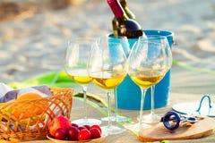 Стекла белого вина на пляже на заходе солнца, тема пикника, Стоковое Фото