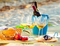 Стекла белого вина на пляже на заходе солнца, тема пикника, Стоковое фото RF