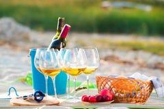 Стекла белого вина на пляже на заходе солнца, тема пикника, Стоковое Изображение RF