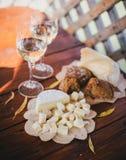 2 стекла белого вина с сыром и хлебом на таблице Стоковое фото RF