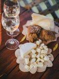 2 стекла белого вина с сыром и хлебом на таблице Стоковое Фото