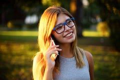 Стекла белокурой девушки нося на улице говоря на телефоне Стоковые Фотографии RF