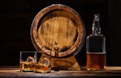 Стекла, бутылка и бочонок вискиа с кубами льда служили на древесине Стоковое Фото