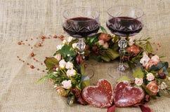 2 стекла вина, венка цветков и конца-вверх 2 сердец Стоковые Изображения