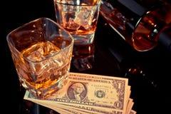 Стекла вискиа около бутылки и долларов на черной таблице Западный стиль темы Стоковое Изображение