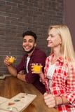 Стекла владением человека и женщины гонки смешивания с апельсиновым соком сидят на деревянном столе в кафе бара Стоковые Фото