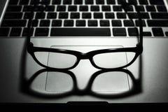 Стекла глаза на свете портативного компьютера низком ключевом стоковые изображения