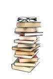 Стекла лежа на куче книг белая предпосылка - вертикальный пэ-аш стоковые фото