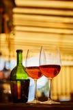 2 стекла заполнили с красным вином и бутылкой в предпосылке Стоковые Изображения RF