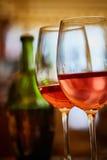 2 стекла заполнили с красным вином и бутылкой в предпосылке Стоковые Фотографии RF
