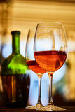 2 стекла заполнили с красным вином и бутылкой в предпосылке Стоковые Изображения