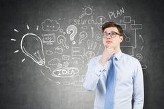 Стекла задумчивого бизнесмена нося и startup эскиз идеи на b Стоковое Изображение