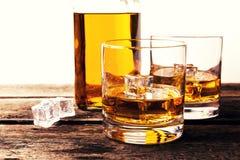 Стекла и бутылка вискиа на деревянном столе против белого backgro Стоковая Фотография
