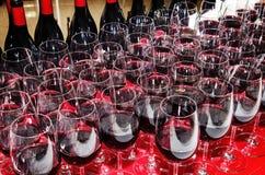 Стекла и бутылки красного вина на таблице партии коктеиля Стоковая Фотография