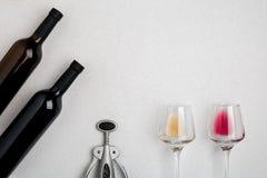Стекла и бутылки красного и белого вина на белой предпосылке от взгляд сверху Стоковое Фото
