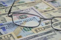 Стекла и деньги банкноты доллара; финансовая предпосылка стоковое фото rf