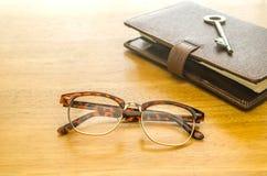 Стекла и коричневый кожаный организатор с ключом Стоковое Фото