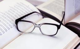 Стекла и открытые книги на таблице Стоковое фото RF