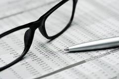 Стекла и ручка на предпосылке отчета о запасе Стоковое Фото