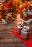 2 стекла какао с взбитым сиропом сливк и шоколада на деревянном столе и доме пряника, копилке и Стоковое Изображение