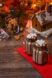 2 стекла какао с зефирами, взбитым сиропом сливк и шоколада на деревянном столе и доме пряника, печенье Стоковая Фотография RF