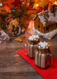 2 стекла какао с зефирами, взбитым сиропом сливк и шоколада на деревянном столе и доме пряника, печенье Стоковое Изображение
