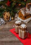2 стекла какао с зефирами, взбитым сиропом сливк и шоколада на деревянном столе и доме пряника, печенье Стоковое Изображение RF