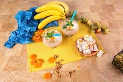 2 стекла коктеиля, грецкие орехи, физалис, высушенные абрикосы, бананы, листья мяты на красочной предпосылке стоковые изображения rf