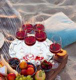 Стекла красного вина на заходе солнца приставают к берегу Стоковое Фото