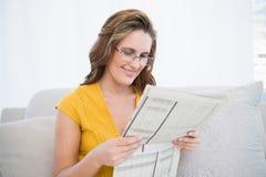 Стекла мирной женщины нося читая газету Стоковое Фото