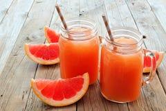 Стекла опарника каменщика сока грейпфрута на деревенской деревянной предпосылке Стоковые Изображения RF