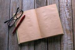 Стекла пишут и книга на деревянной таблице для жулика дела или образования Стоковые Изображения