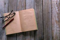 Стекла пишут и книга на деревянной таблице для жулика дела или образования Стоковые Изображения RF