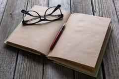 Стекла пишут и книга на деревянной таблице для жулика дела или образования Стоковое фото RF