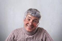 Стекла положительного жизнерадостного человека вида зрелого нося смотря добросердечно в камеру имея нежную улыбку Усмехаясь старш стоковое фото