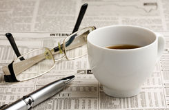 Кофе и ручка стекел на газете Стоковое Фото