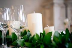 Стекла, свечи и свежие зеленые цвета на таблице свадьбы Стоковая Фотография RF