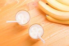 2 стекла сока банана на таблице рядом с желтым зрелым b Стоковые Фото