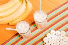 2 стекла сока банана на таблице рядом с желтым зрелым b Стоковое Изображение