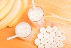 2 стекла сока банана на таблице рядом с желтым зрелым b Стоковое фото RF