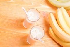 2 стекла сока банана на таблице рядом с желтым зрелым b Стоковое Изображение RF