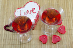 2 стекла с красными алкогольным напитком и сердцем сформировали свечи Стоковые Фотографии RF