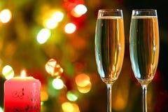 Стекла с шампанским и свечой против праздничных светов стоковая фотография rf