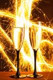 Стекла Шампани против предпосылки бенгальского огня Стоковые Изображения