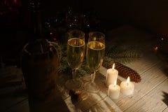 2 стекла шампанского, бутылки вина и накаляя свечей помещены на таблице украшенной с конусами Стоковое Фото