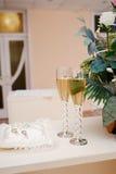 2 стекла шампанского и подушки с кольцами на таблице для свадебной церемонии Стоковое Изображение
