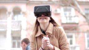 Стекла шлемофона виртуальной реальности vr молодой счастливой девушки нося имея потеху играя снаружи на улице в беже outwear паль видеоматериал