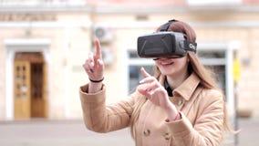 Стекла шлемофона vr виртуальной реальности технологии виртуального пространства молодой женщины нося в бежевом пальто имея потеху сток-видео